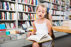Little smart girl reading a book in the school library Royalty Free Stock Photography