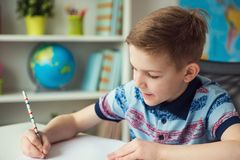 Little smart school boy making homework at desk in room. Little smart school boy making homework at desk in his room royalty free stock photos