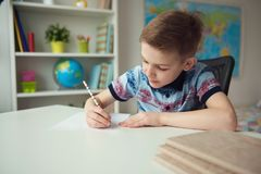 Little smart school boy making homework at desk in room. Little smart school boy making homework at desk in his room stock photos