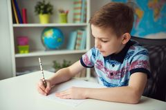 Little smart school boy making homework at desk in room. Little smart school boy making homework at desk in his room stock photo