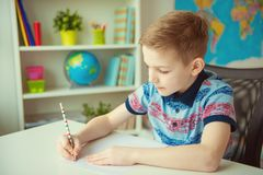 Little smart school boy making  homework at desk in room. Little smart school boy making  homework at desk in his room royalty free stock images