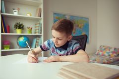 Little smart school boy making homework at desk in room. Little smart school boy making homework at desk in his room royalty free stock photo