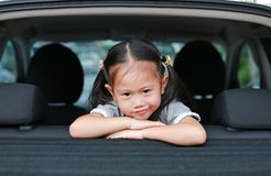 Little smile of Asian child girl looking camera from hatchback door of the car stock images