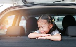 Little smile of Asian child girl looking out from hatchback door of the car royalty free stock image