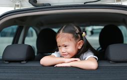 Little smile of Asian child girl looking out from hatchback door of the car stock photos
