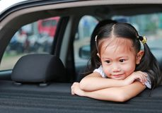 Little smile of Asian child girl looking out from hatchback door of the car stock images