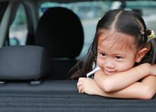 Little smile of Asian child girl looking out from hatchback door of the car stock photo
