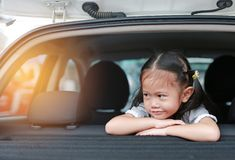 Little smile of Asian child girl looking out from hatchback door of the car stock image