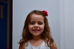 The little smiles girl with a flower in her hair.  royalty free stock photo