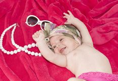 Little smiley baby girl on red blanket Royalty Free Stock Images