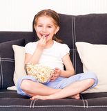 Little girl watching TV. Little smiley girl eating popcorn in front of TV Royalty Free Stock Photo