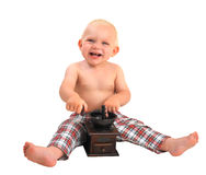 Little smiling baby boy with coffee grinder wearing plaid pants Royalty Free Stock Photography