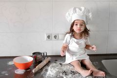 Little smiling baby girl baker in white cook hat and apron kneads a dough on tle kitchen.  Royalty Free Stock Image