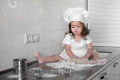 Little smiling baby girl baker in white cook hat and apron kneads a dough on tle kitchen.  Royalty Free Stock Photography