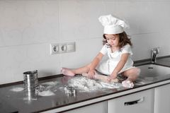 Little smiling baby girl baker in white cook hat and apron kneads a dough on tle kitchen.  Royalty Free Stock Photo