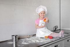 Little smiling baby girl baker in white cook hat and apron kneads a dough on tle kitchen royalty free stock photo