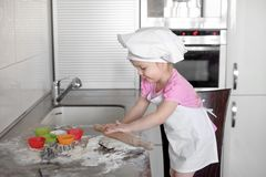 Little smiling baby girl baker in white cook hat and apron kneads a dough on tle kitchen.  Stock Photo