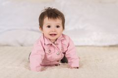 Little smiling baby girl crawling on bed stock image