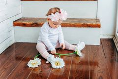 Little baby girl wearing spring wreath siting on floor in bright light living room near window and playing with gerbera. Little smiling baby girl one year old stock images