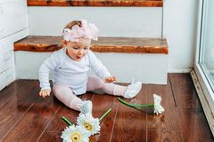 Little baby girl wearing spring wreath siting on floor in bright light living room near window and playing with gerbera. Little smiling baby girl one year old royalty free stock photography