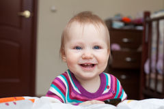 Little smiling baby girl standing near the bed Stock Photography