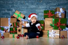 Little smiling baby santa claus in christmas hat and business suit . Happy new year and merry christmas. Holidays and gifts for. Children royalty free stock images