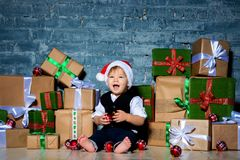 Little smiling baby santa claus in christmas hat and business suit . Happy new year and merry christmas. Holidays and gifts for. Children royalty free stock photography