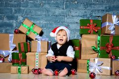 Little smiling baby santa claus in christmas hat and business suit . Happy new year and merry christmas. Holidays and gifts for. Children royalty free stock photos