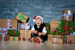Little smiling baby santa claus in christmas hat and business suit . Happy new year and merry christmas. Holidays and gifts for. Children royalty free stock photo