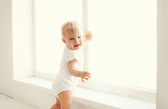 Little smiling baby in white room home stands near window Stock Photos