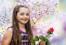 Little girl holding a rose. Little smiling beautiful girl holding a rose Stock Photo