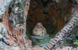 Little smiling bhudda in a small cave. This is a miniature small rock garden with a little smile bhudda in a small cave Stock Photos