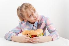 Little smiling blond girl with big hamburgers Royalty Free Stock Photography