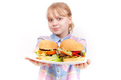 Little smiling blond girl with big hamburgers Stock Photo