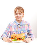 Little smiling blond girl with big homemade hamburgers Royalty Free Stock Images