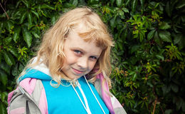 Little smiling blond girl in casual sport clothes. Little blond girl wears casual sport clothes. Outdoor smiling portrait above green leaves background Royalty Free Stock Photos