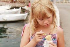 Little smiling blond girl eats ice cream Stock Photo