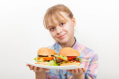 Little smiling blond girl with homemade hamburgers Stock Photos