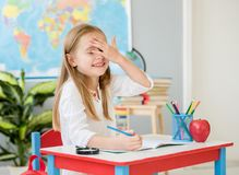 Little smiling blond girl made a mistke writing in the school classroom royalty free stock photography
