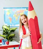 Little smiling blond girl holding huge red pencil in the school classroom royalty free stock photo