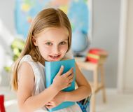 Little smiling blond girl holding blue book in the school class Royalty Free Stock Photos