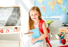 Little smiling blond girl standing in the school classroom Royalty Free Stock Images