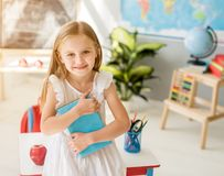Little smiling blond girl standing in the school classroom stock image