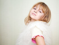 Little smiling blond girl in white fluffy fur vest Stock Photos