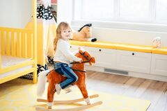 Free Little Smiling Blonde 3 Years Old Girl Sitting On Rocking Horse In Yellow Bedroom At Home In Day Time. Time To Play During Self Stock Photo - 179278680