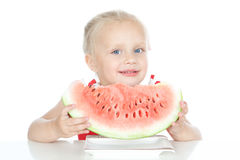 Little smiling blonde girl eating a watermelon Stock Image
