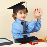 Little smiling boy in academic hat conducts scientific research with microscope Royalty Free Stock Photo