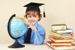 Little smiling boy in academic hat with geographical globe Stock Photography