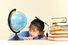 Little smiling boy in academic hat looks at geographical globe Royalty Free Stock Photos