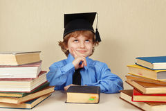 Little smiling boy in academic hat among old books Royalty Free Stock Image